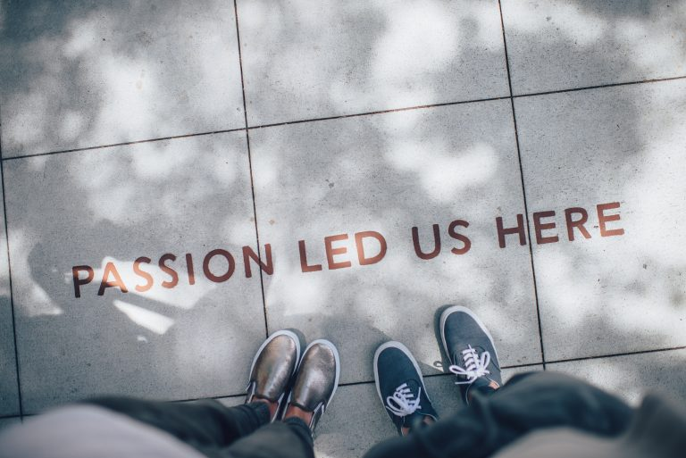 Photo of feet on a sidewalk that reads 'Passion led us here'